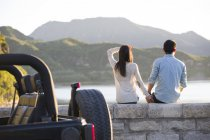 Chinese couple sitting on lakeside in suburbs — Stock Photo