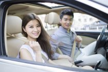 Chinese couple sitting in car — Stock Photo
