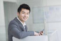 Homem de negócios chinês sentado com smartphone no escritório — Fotografia de Stock
