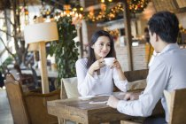 Chinese woman and man sitting in cafe together — Stock Photo