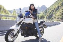 Chinesin sitzt auf Motorrad mit Helm — Stockfoto