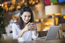 Chinese woman using smartphone and laptop in cafe — Stock Photo