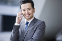Chinese businessman talking on phone and smiling — Stock Photo