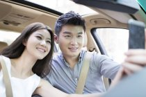 Chinese couple sitting in car and taking selfie — Stock Photo
