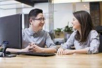 Colaboradores chinos hablando en la oficina - foto de stock