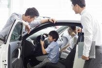 Chinese family with son choosing car with dealer — Stock Photo