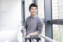 Китайский бизнесмен держит чашку кофе в офисе — стоковое фото