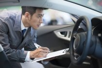 Close-up of auto mechanic making notes in car — Stock Photo