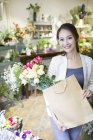 Chinese woman standing with floral bouquets in store — Stock Photo