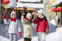 Chinese children holding candied haws and looking in camera — Stock Photo