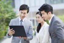 Hommes d'affaires chinois travaillant avec portable sur rue — Photo de stock