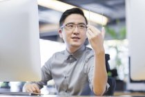 Chinese IT worker developing smartphone in office — Stock Photo