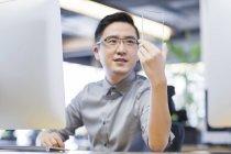 Lavoratore cinese si sviluppa lo smartphone in ufficio — Foto stock
