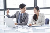 Chinese business people using laptop in meeting — Stock Photo