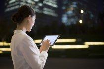 Empresaria China uso de tableta digital, vista trasera - foto de stock