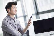 Hombre de negocios chino con smartphone en la oficina - foto de stock