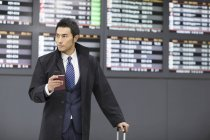 Chinese businessman waiting in airport with passport and smartphone — Stock Photo