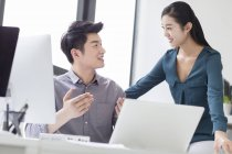 Chinese business co-workers talking in office — Stock Photo