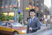 Chinese businessman standing on street at car — Stock Photo