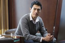 Portrait of pensive Chinese businessman in hotel room — Stock Photo