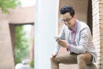 Китаец сидит на камне и использует смартфон — стоковое фото
