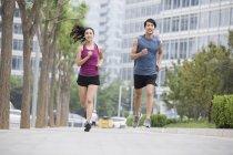 Китайская пара бегает вместе по улице — стоковое фото