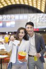 Chinese couple standing with popcorn and drinks in movie theater — Stock Photo