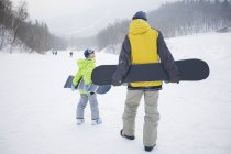 Father and son walking with snowboards on snow — Stock Photo