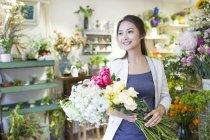 Китайская женщина, стоя с цветочные букеты в магазине — стоковое фото