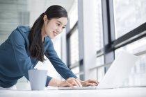 Китайская предпринимательница использует ноутбук в офисе — стоковое фото