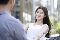 Casal chinês de mãos dadas e a sorrir na rua — Fotografia de Stock
