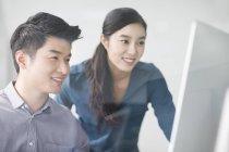 Colegas chineses usando computador no escritório — Fotografia de Stock