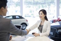 Empresaria china haciendo trato con vendedor de coches en sala de exposición - foto de stock