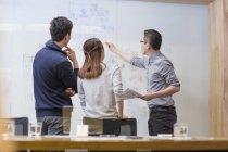 Travailleurs informatiques chinois ayant une réunion dans la salle de conseil — Photo de stock