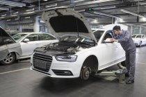 Chinese auto mechanic working in repair shop — Stock Photo