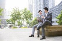 Китайские бизнесмены обсуждали работу на скамейке — стоковое фото