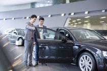 Chinese car dealer helping client choosing car in showroom — Stock Photo