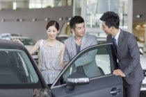 Chinese car dealer helping couple choosing car in showroom — Stock Photo