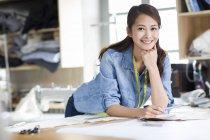 Créateur de mode chinois appuyé sur la table en studio et souriant — Photo de stock