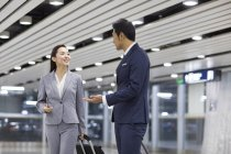Chinese business people talking in airport with suitcases — Stock Photo