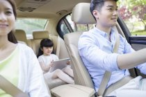 Chinese family riding in car together — Stock Photo