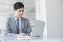Empresário chinês usando laptop no escritório — Fotografia de Stock