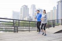 Взрослая пара из Китая бегает по городскому мосту — стоковое фото
