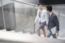 Chinese business people walking up stairs and talking — Stock Photo