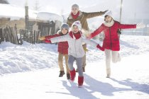 Chinese family running in snow with arms outstretched — Stock Photo
