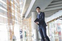 Homme d'affaires chinois marchant dans l'aéroport avec valise et ordinateur portable — Photo de stock