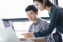 Compañeros de negocio chinos utilizando la computadora portátil en la oficina - foto de stock