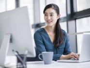 Китайская предпринимательница работает с ноутбуком в офисе — стоковое фото