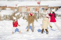 Китайські родини з для дітей мають сніжок боротьби в селі — стокове фото