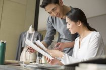 Chinese fashion designers holding sketches at table — Stock Photo